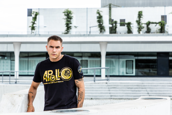 A man is leaning against a fence looking at the camera. He is wearing a black Alpha Industries t-shirt with a gold pattern on the front.