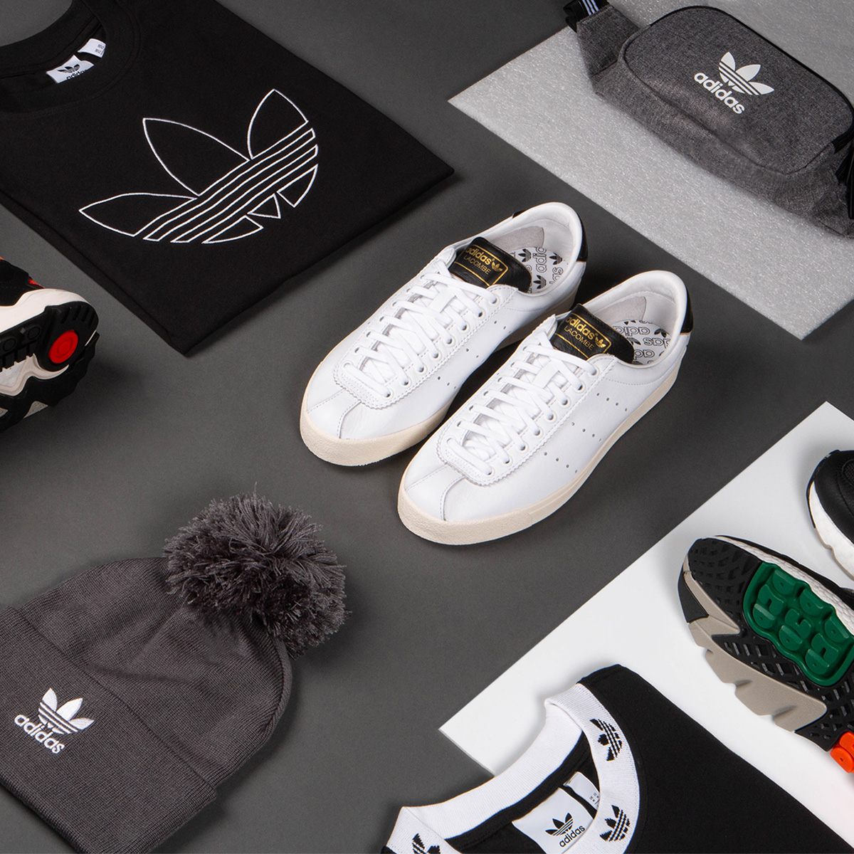Adidas trainers are in the centre of a grey floor, surrounded by a neatly folded adidas t-shirt, adidas bum-bag, and an adidas beanie in shades of grey, white and black.