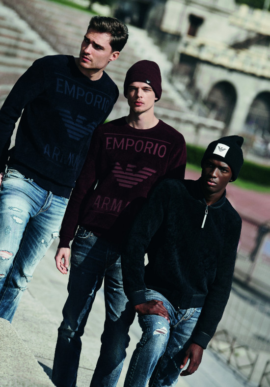 Three men walk down the street wearing black emporio armani jumpers