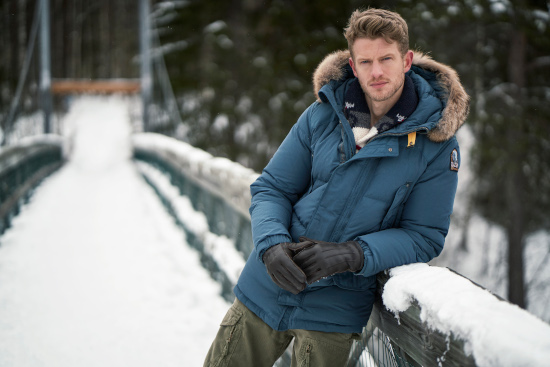 A man is leaning against a bridge railing wearing a blue parka coat from Parajumpers with a fur hood.