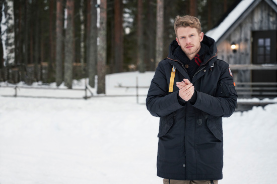 A man is stood in the snow wearing a black parajumpers parka coat