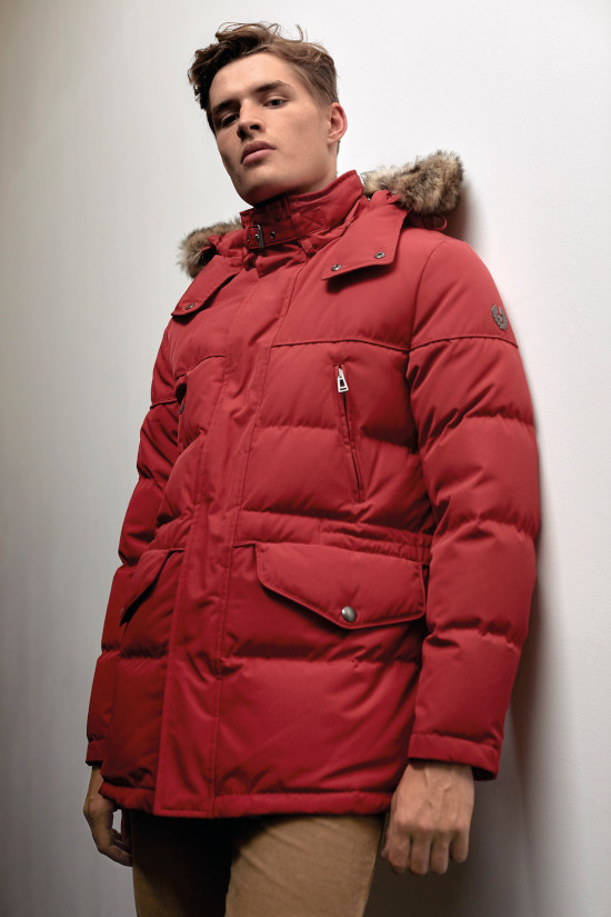 A man is looking down at the camera wearing a bright red parka coat from Belstaff