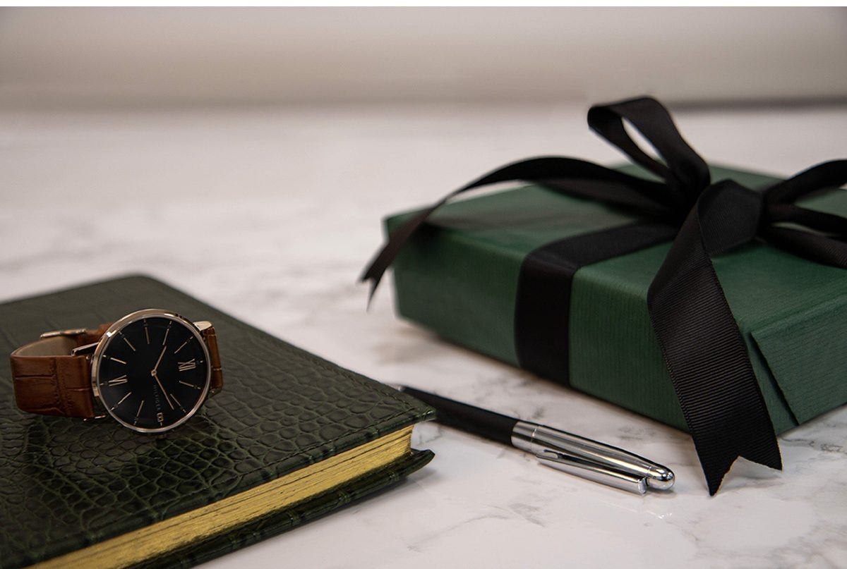 A neatly wrapped gift with black ribbon and green wrapping paper.