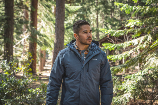 A man wearing a blue Columbia coat in the forest