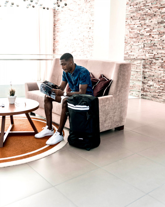 A man is sat on a white couch reading a magazine. A black Eastpak suitcase is on the floor next to him