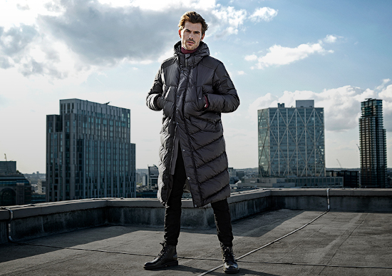 A man is stood on top of a roof in a city. He is wearing a long G-Star Raw puffer coat and has his hands in his pockets.