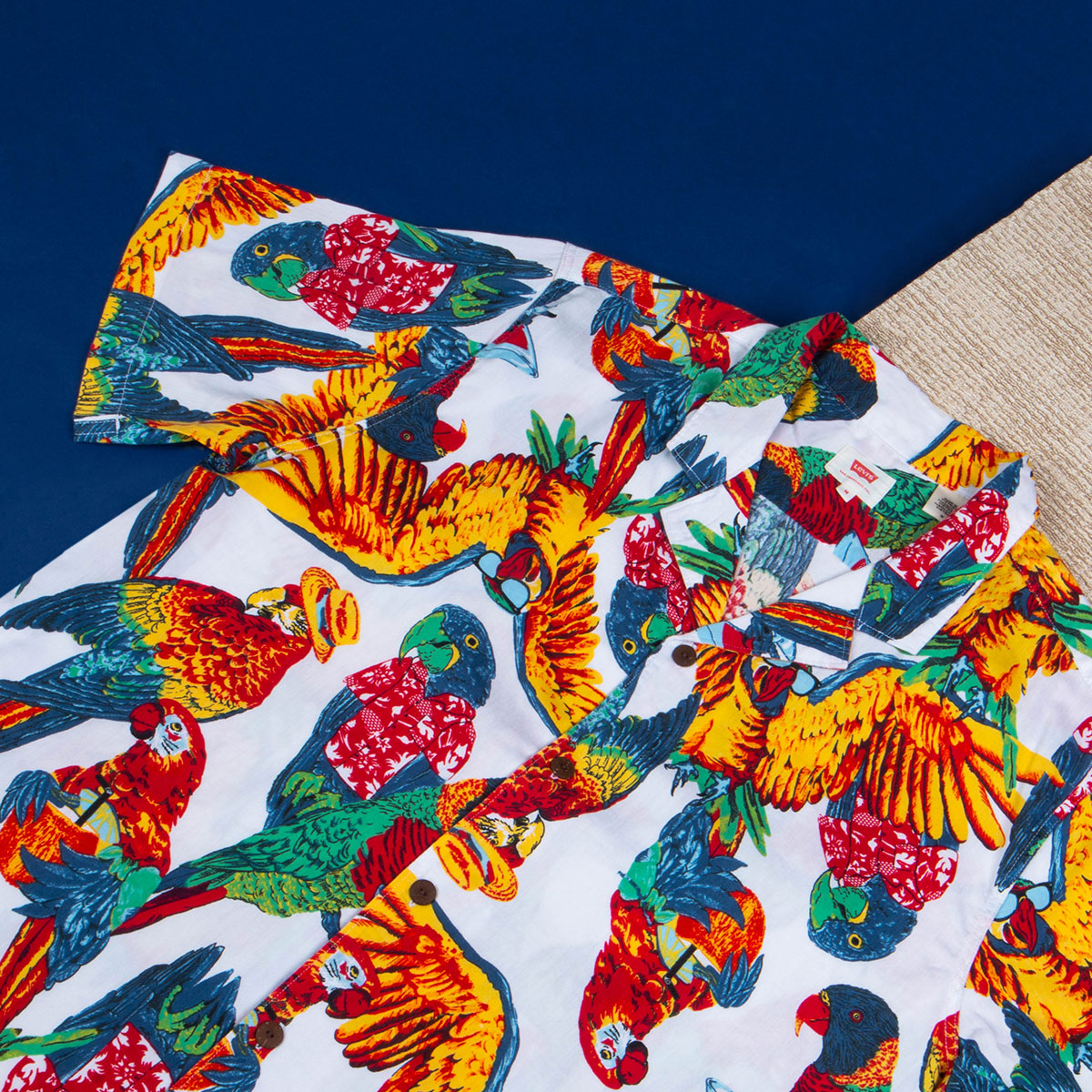A white Levis cuban collar shirt with bright parrots printed onto it