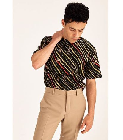 Rami Malek is stood with a hand on his neck wearing beige trousers and an 80s print shirt