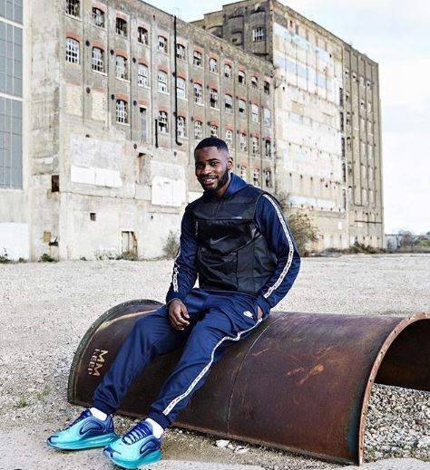 Dave is sat outside a large factory, wearing a blue Nike tracksuit and Nike trainers.