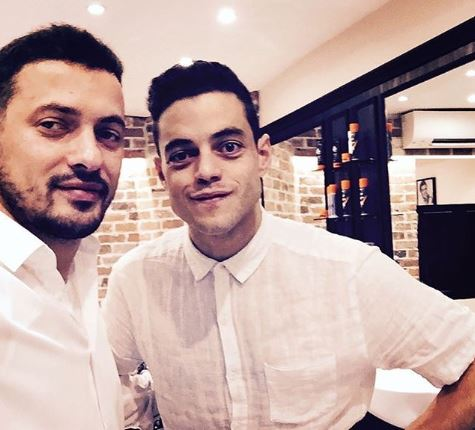 Rami Malek is smiling at the camera wearing a white, short-sleeved shirt.