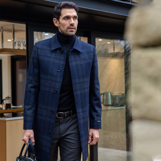 A man walking out of a building wearing a smart jumper matched with a blue overcoat, grey chinos and a designer suitcase.