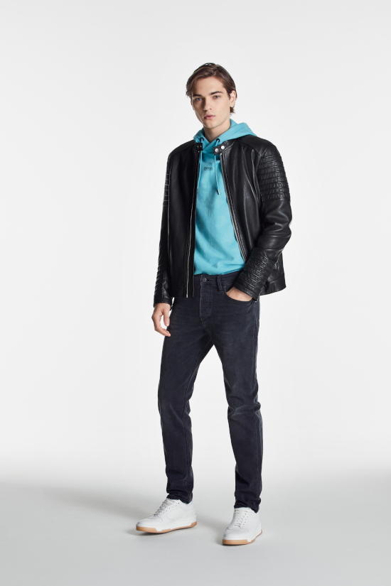 A man is stood against a grey background. He is wearing a black Hugo Boss leather jacket with a blue hoodie and blue slim fit jeans. He has one hand in his pocket.