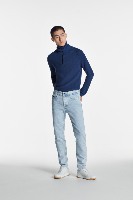 a man is stood against a grey background looking to the side. He is wearing a blue roll neck jumper and light slim fit jeans from Boss Casual.