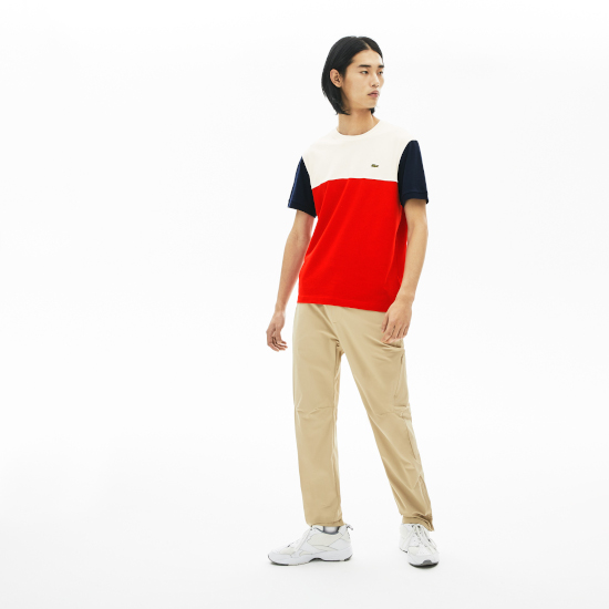 A man wearing a red and white striped polo shirt and some brown chinos.