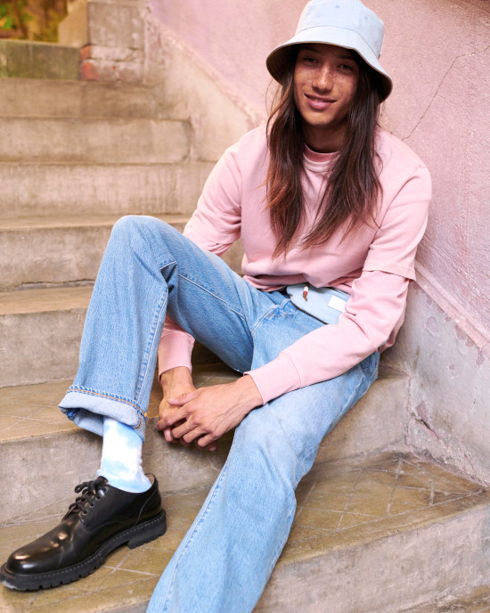 A man wearing Levis jeans and a pink Levis jumper