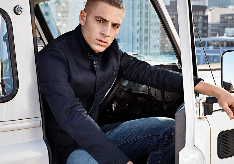A man leaning out a car wearing a black G Star Raw jacket