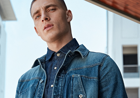 A man looking at the camera wearing a denim g star raw jacket