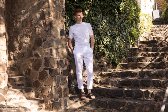 A man wearing birkenstocks, a white t shirt and white trousers. It's a bold look.