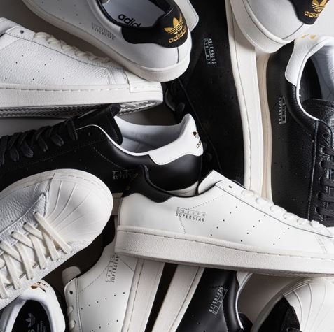 a pile of adidas originals pure superstar trainers in white and black