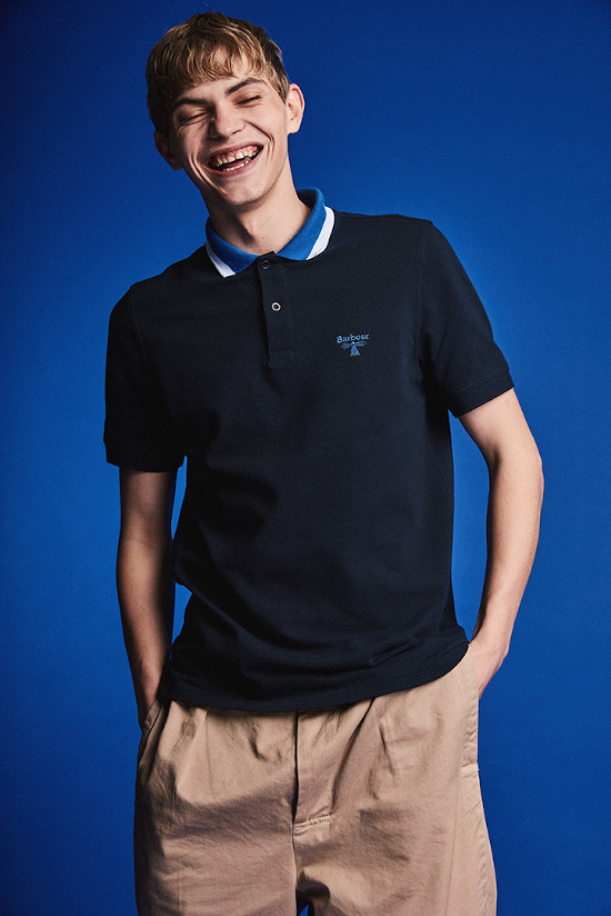a man is laughing to the camera wearing beige shorts and a dark blue Barbour Beacon polo shirt