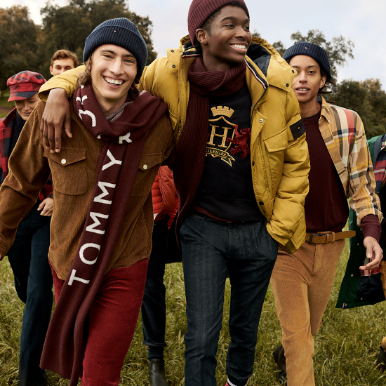 A group of men laugh at the camera, wearing Tommy Hilfiger coats, scarfs, hats and trousers