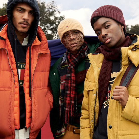 A group of men are staring into the camera, wearing Tommy Hilfiger jackets, jumpers, hats and scarfs